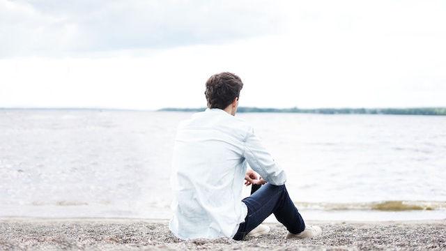 ein Mann, der am Meer sitzt