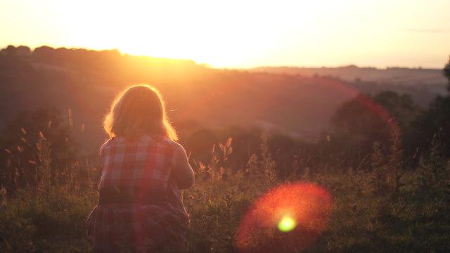 ein Mädchen, das den Sonnenuntergang beobachtet